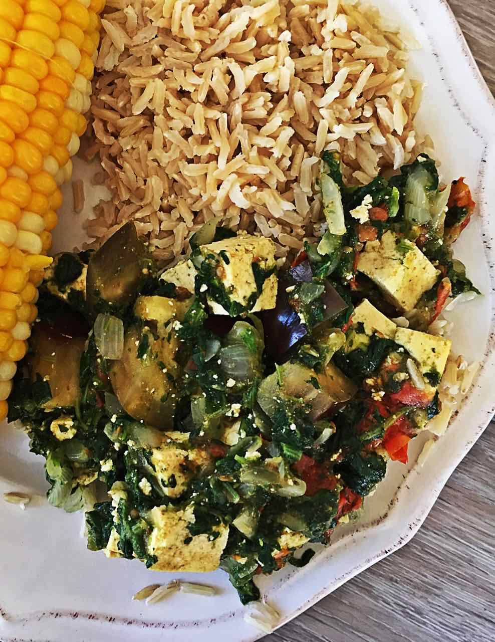 Image of Vegan Indian Palak Paneer with tofu and eggplant on plate with basmati rice and corn on the cob.