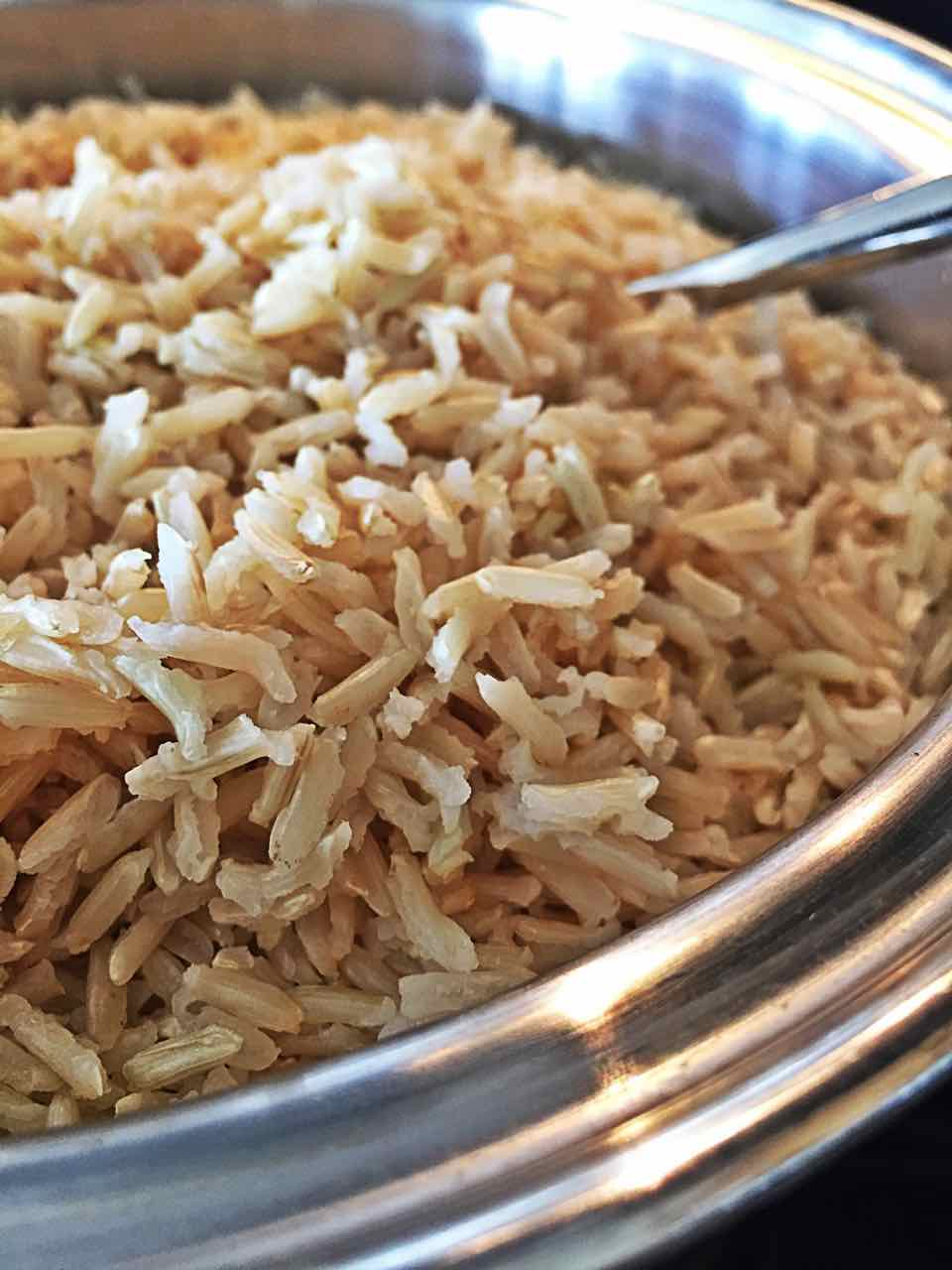 Image of fluffy brown basmati rice, which also goes great with this vegan spinach Indian side dish.