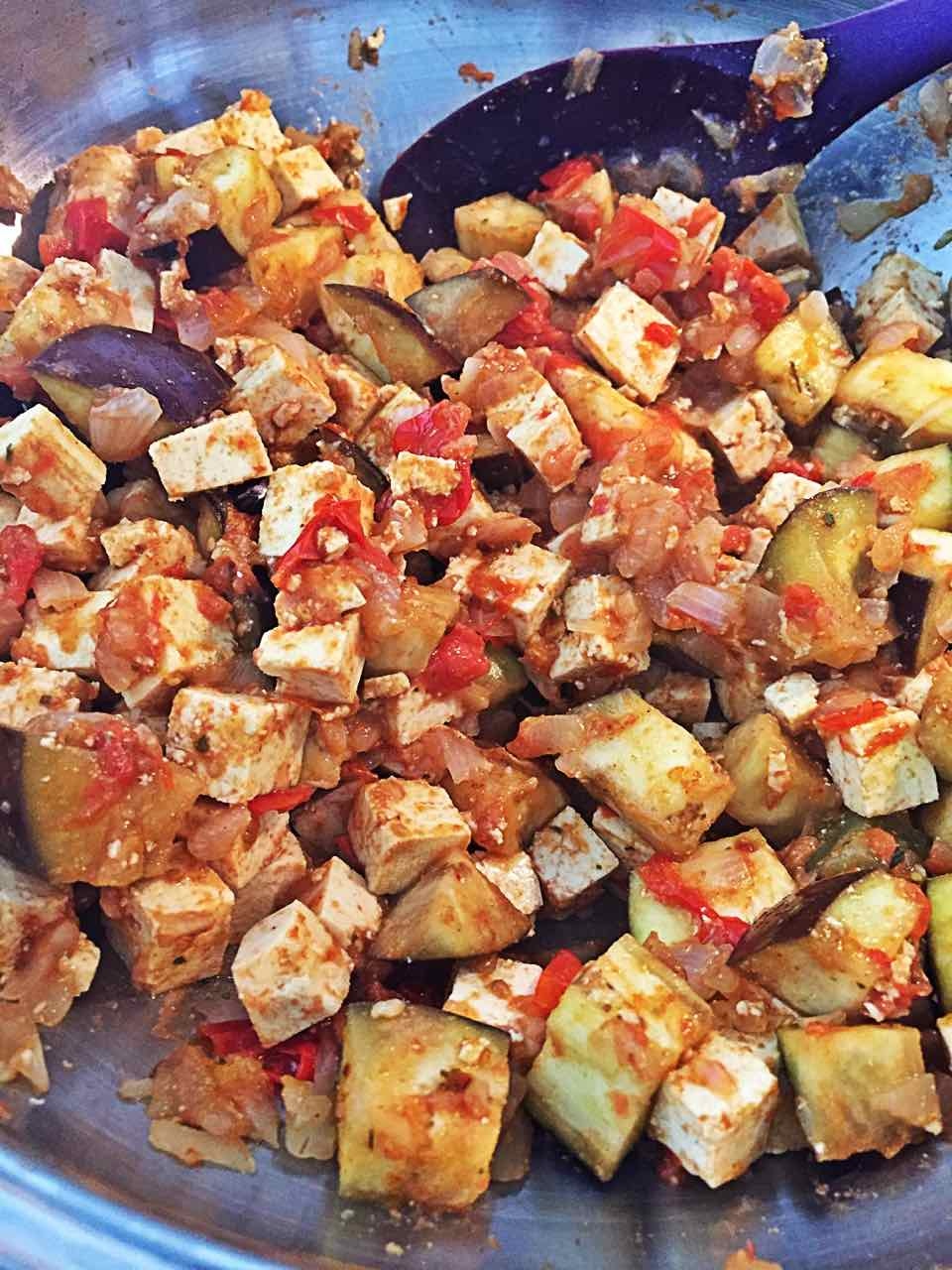 Image of the first steps of this vegan Indian spinach side dish recipe: tofu as a paneer substitute with cubed eggplant, onions, spices and fresh blended tomatoes.