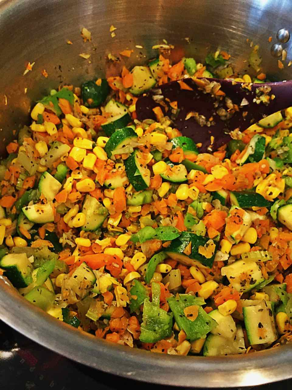 Image of vegetables cooking in a pot, ready for the soup broth to be added.