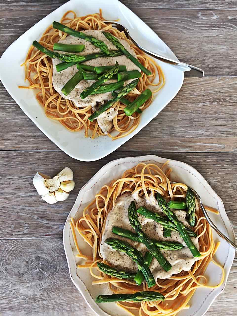 Image of two plates of vegan creamy pesto linguine with asparagus