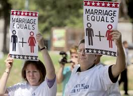 """Woman and man holding signs that read """"marriage equals"""" with a figure of a man and a woman"""