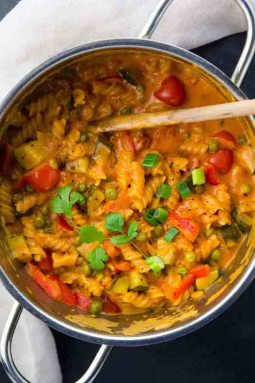 a pot of vegan one pot pasta with peas, zucchini, and bell peppers and a wooden spoon on a black counter top with a grey dish cloth