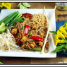 vegan pad thai on a white plate with blue napkin and flowers on the side.