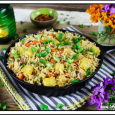 Fully cooked vegan pineapple fried rice in a cast iron skillet on a striped napkin. Purple and orange flowers on the side.