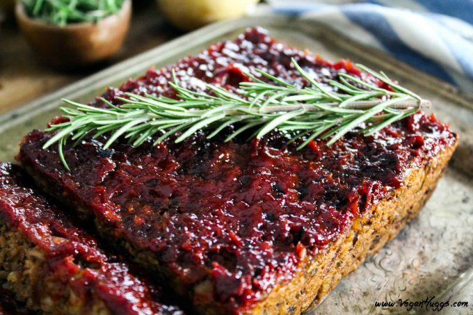 Overhead view of vegan meatloaf on a silver serving plate. Topped with ketchup glaze and fresh rosemary.