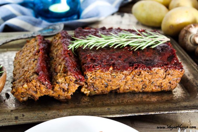 side view of meatless loaf on a silver serving tray. Potatoes and mushrooms in the background.
