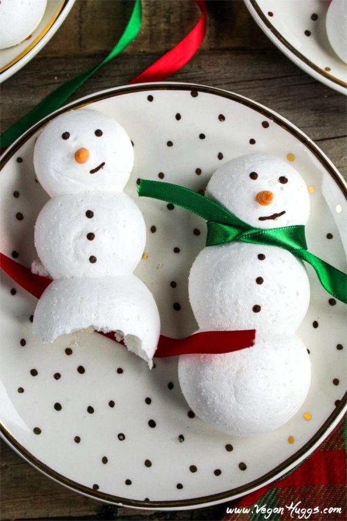 two vegan meringue cookies on a plate. One cookie has a bite taken out.