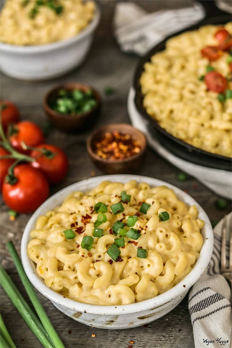 Closeup photo of Vegan Mac n Cheese in a white bowl. Filled white bowl and skillet in background.