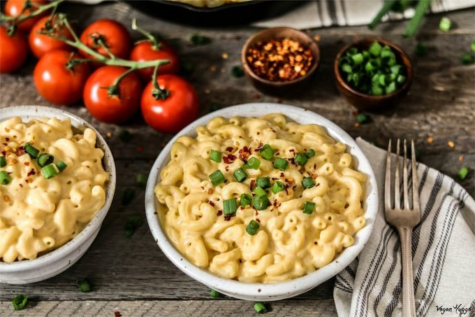 Two white bowls filled with macaroni and topped with green onions.