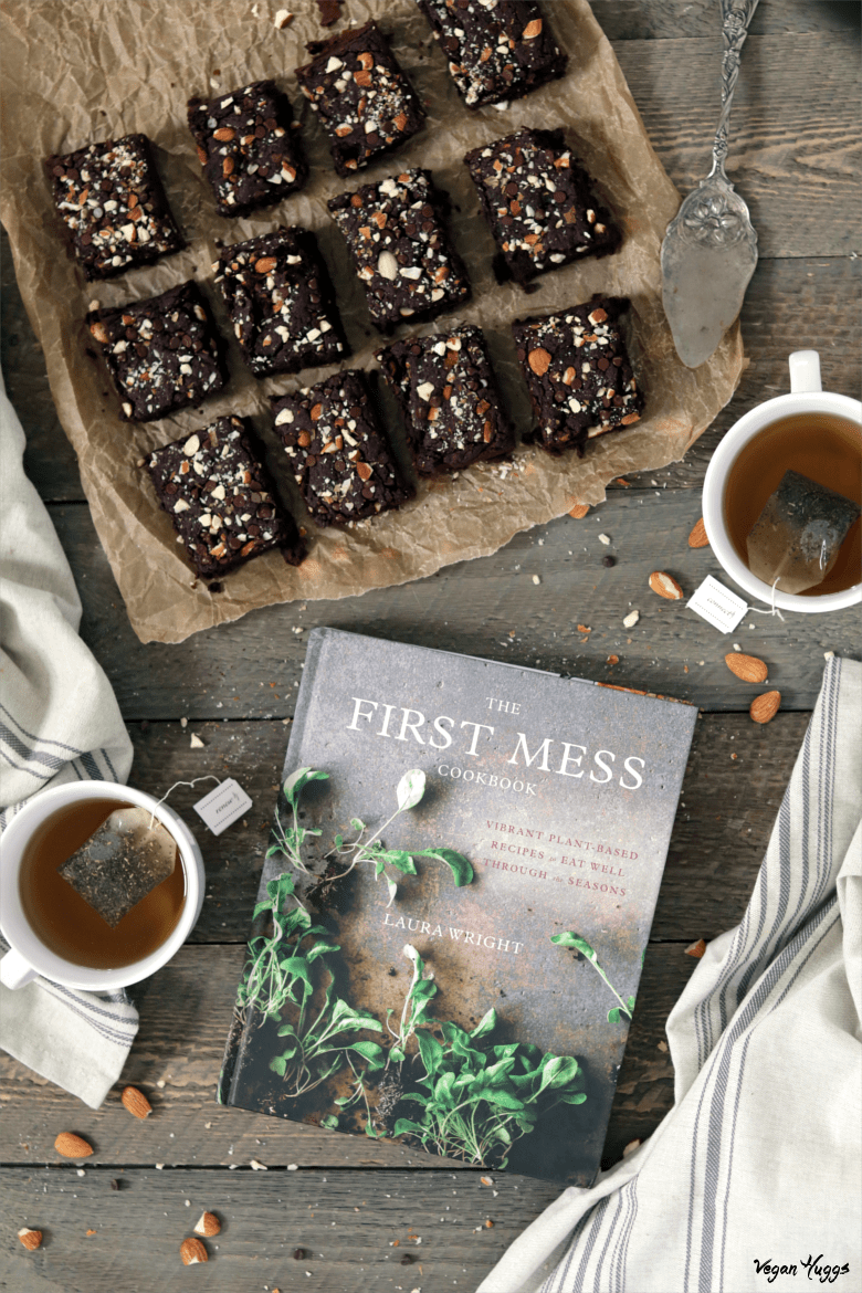 Overhead view of Fudgy Chocolate Brownies on parchment paper. Tea and cookbook on the side.