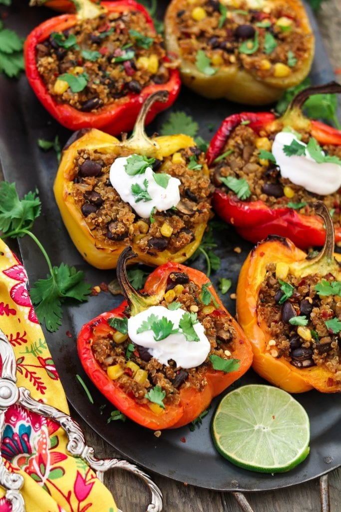 six stuffed peppers on a platter.