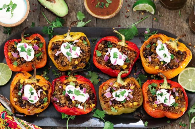 8 Quinoa Stuffed Peppers topped with sour cream, red onion and cilantro.