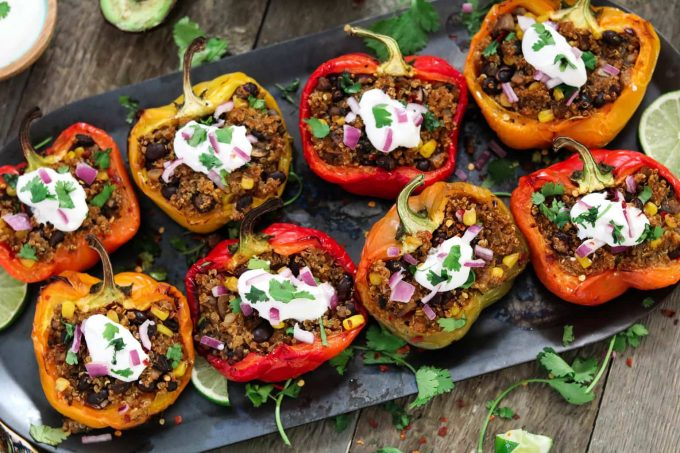8 stuffed peppers diagonally on a pan. Fully loaded with sour cream, red onion and cilantro.