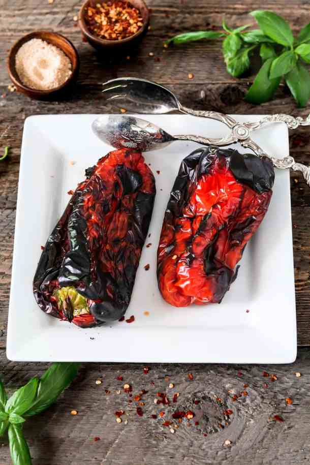 Two roasted red peppers on a white dish