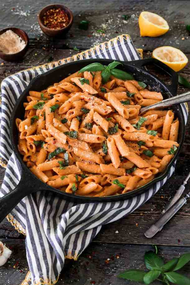Roasted Red Pepper Pasta in a cast iron skillet with striped napkin. Garnished with fresh basil.