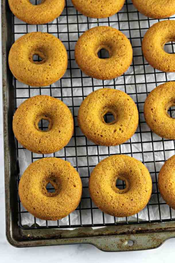 Fully baked vegan pumpkin donuts on a wire cooling rack.