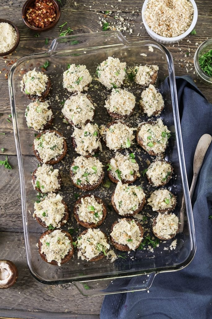 Glass baking dish filled with stuffed mushrooms before they go into the oven.