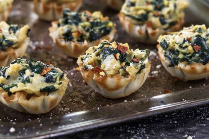 Vegan Spinach Artichoke cups in phyloo shells on a tray.