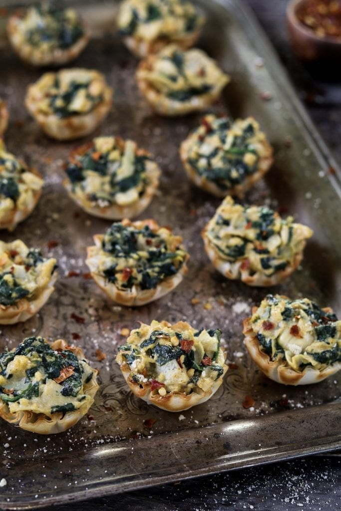 Vertical photo of fully baked Vegan Spinach Artichoke Cups on a tray.