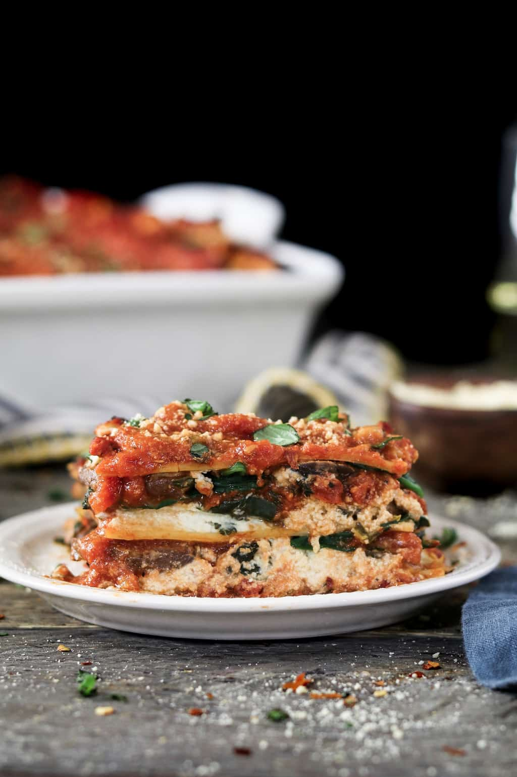 Side view of vegan mushroom lasagna on a white plate and topped with basil.