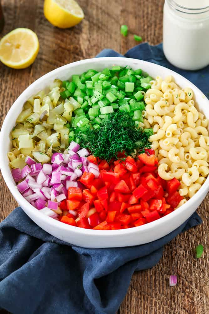 Chopped ingredients in a white bowl for vegan macaroni salad.