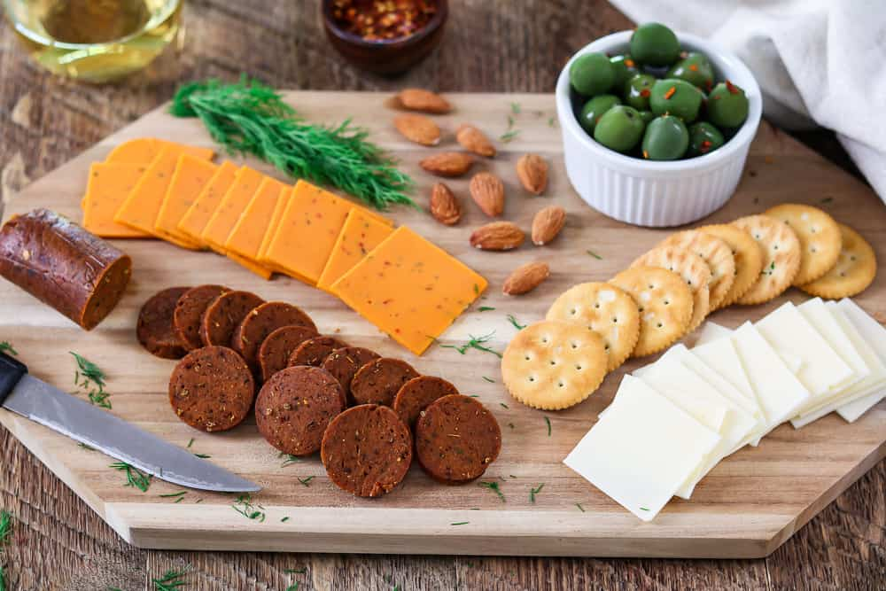 Full shot of snack board with vegan cheese, almonds, fresh dill, crackers and vegan pepperoni recipe. White wine on the side.