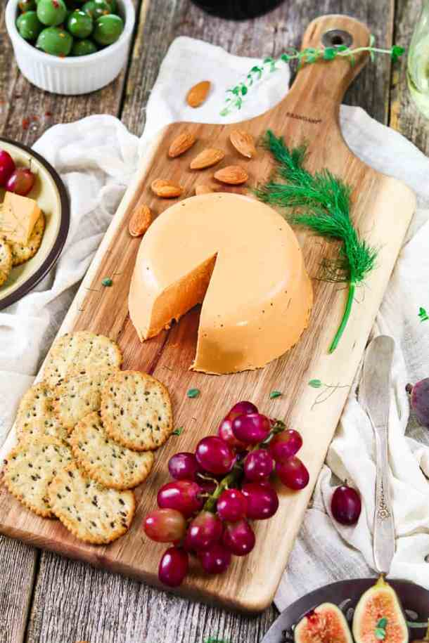 Sideview of vegan cheddar cheese wheel. Glass of wine on the side with olives and a small plate with cheese.