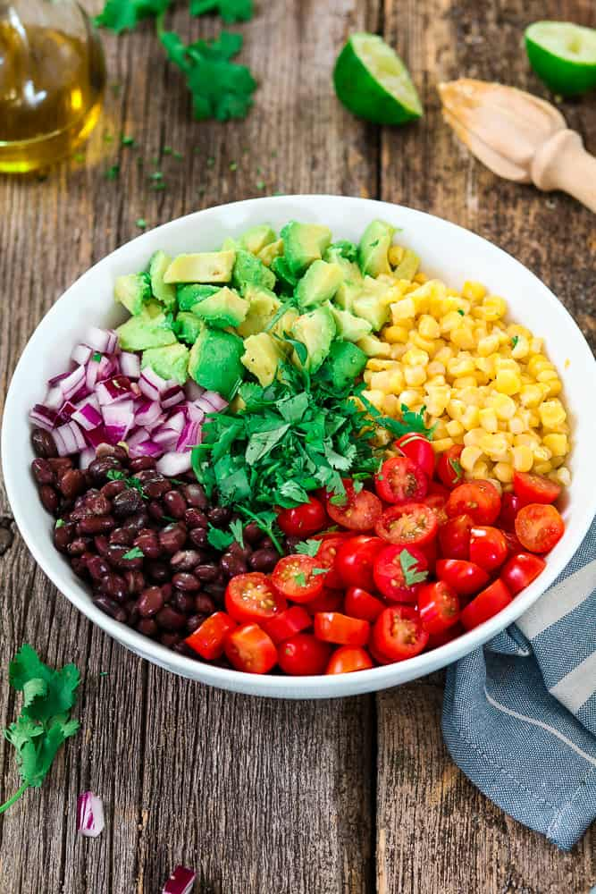 separate sections of corn, tomatoes, avocado, black beans, red onion and cilantro.