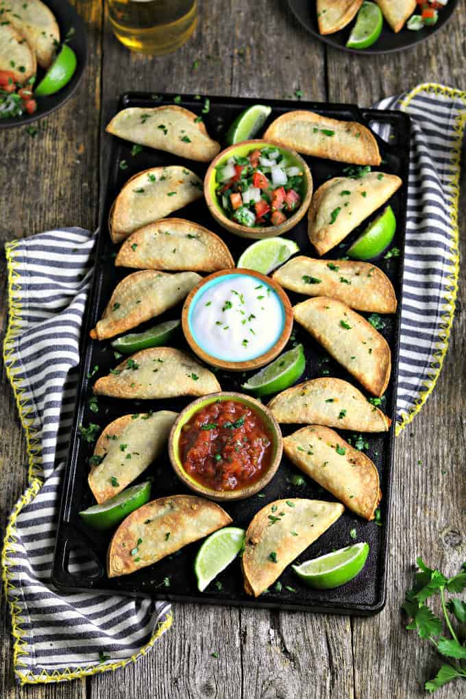 black serving tray filled with fully cooked air fryer tacos. 3 dips in the middles and lime wedges on the side.