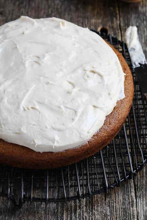 cake on a cooling rack that is partially frosted with vegan cream cheese frosting.