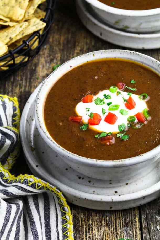 Close up view of Mexican black bean soup in a white bowl, topped with vegan sour cream, green onions and tomatoes.