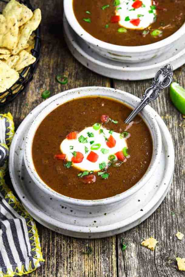 two white bowls filled with Mexican black bean soup and tortilla chips on the side.