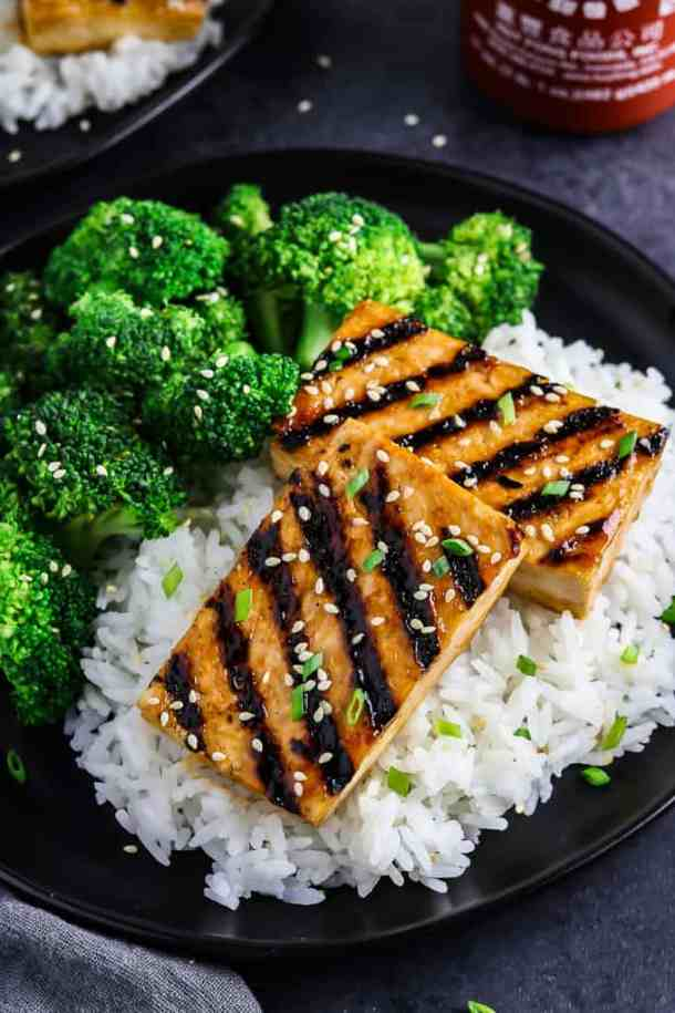 overhead view of two pieces of tofu on a bed of rice and broccoli on the side. Hot sauce in the background.
