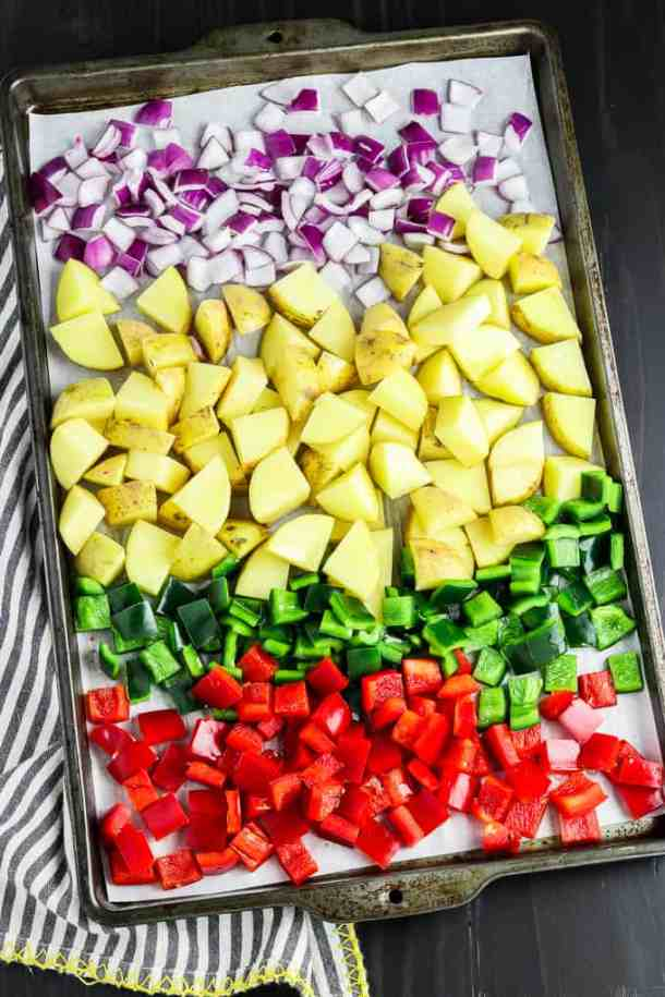 Process photo of a baking sheet filled with cut onions, peppers and potatoes.