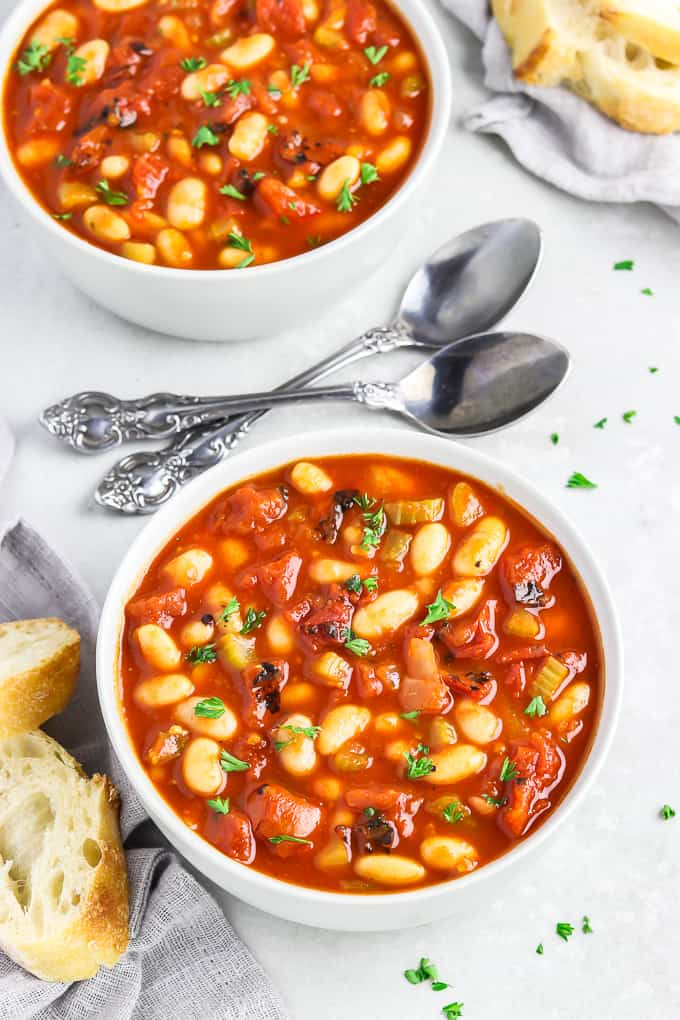 Two bowls of tomato white bean soup topped with parsley and spoons in the middle.