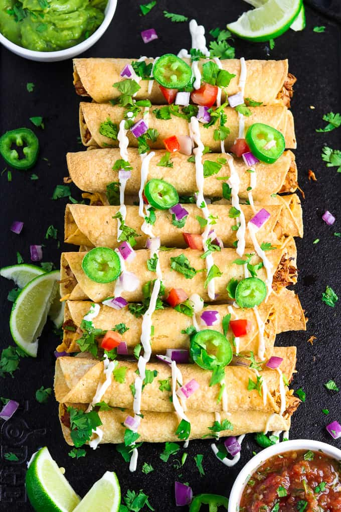 Overhead view of baked taquitos on a black tray with toppings.