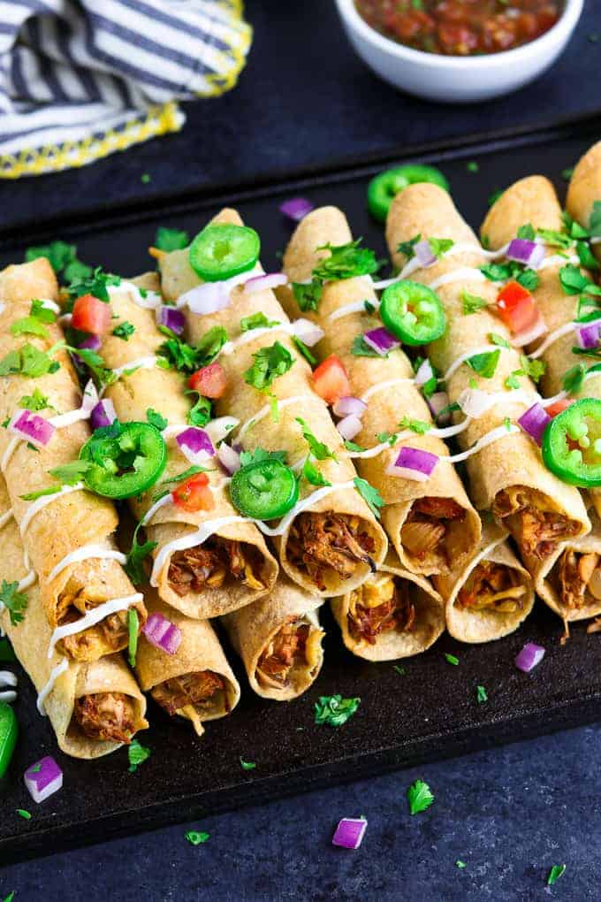 Overhead view of stacked taquitos on a black tray with salsa and napkin in the back.
