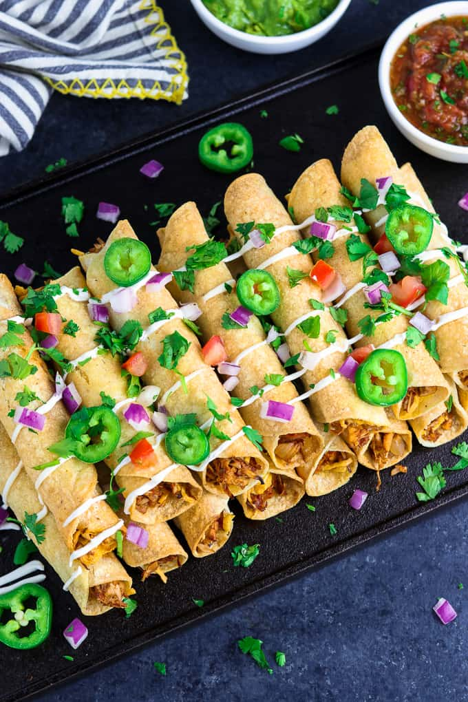 Overhead view of taquitos on a black tray with guacamole and salsa on the side.