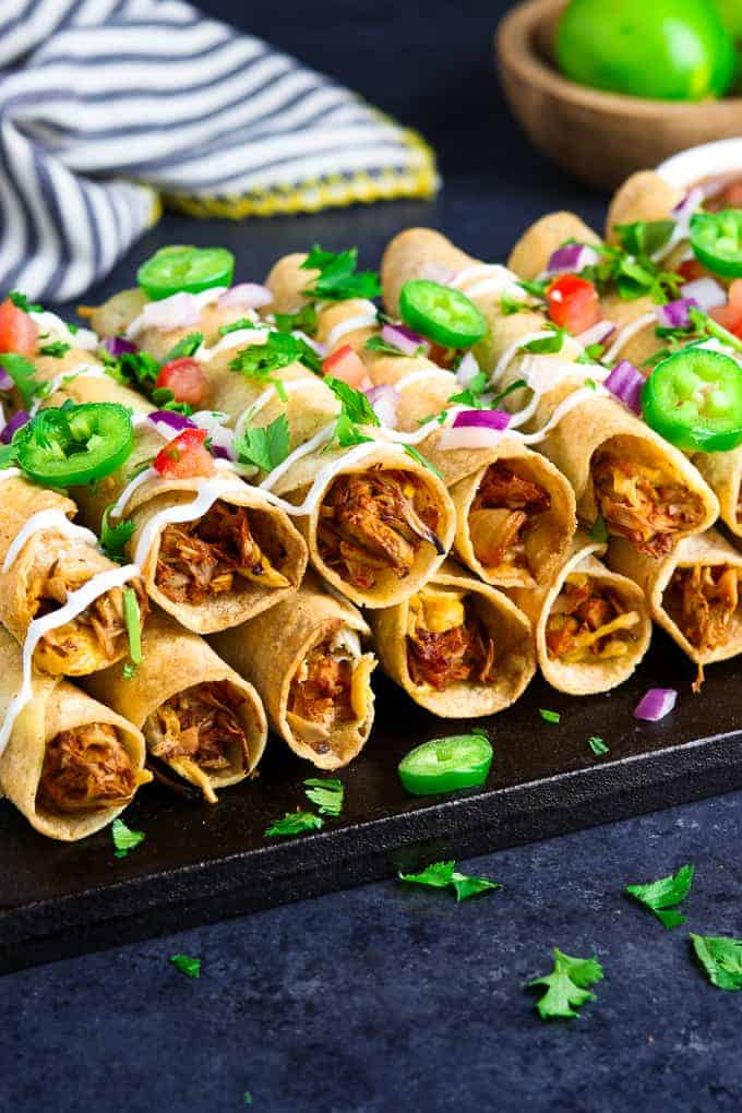 Closeup view of vegan taquitos on a black tray with striped napkin and lime in the background.