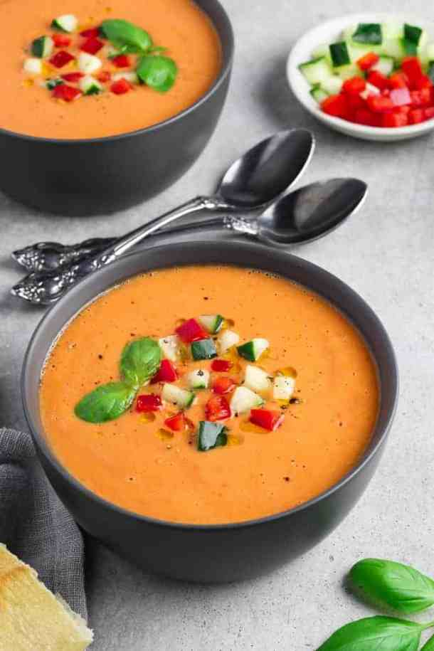 Two bowls filled with gazpacho and topped with cucumbers, belle peppers and basil.