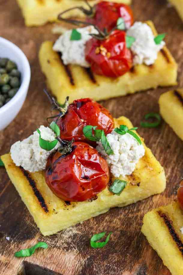 Grilled polenta on a cutting board with capers on the side.