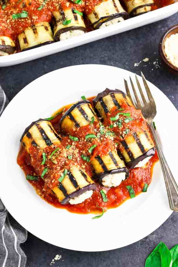 overhead view of 3 pieces of eggplant rollatini on a white dish with fork on the side.
