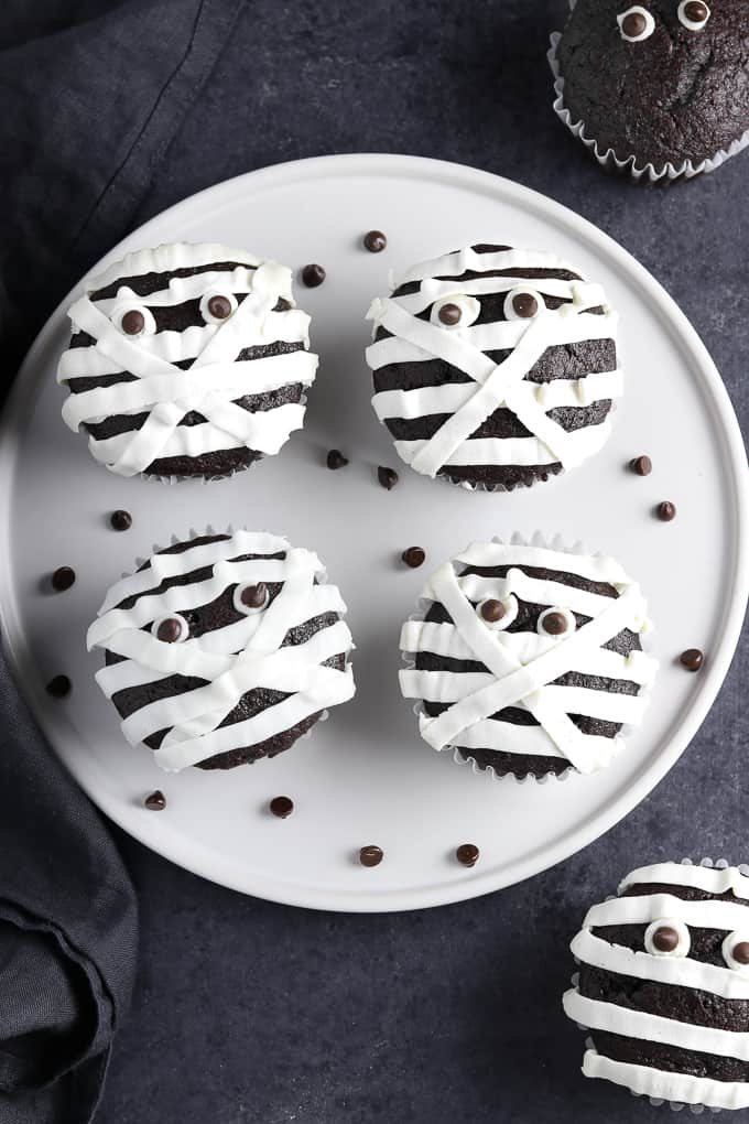 4 mummy cupcakes on a white plate with chocolate chips on the side.