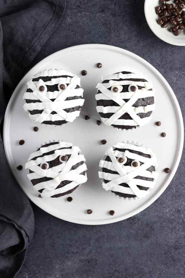 overhead view of 4 mummy cupcakes on a white plate with black napkin on the side.