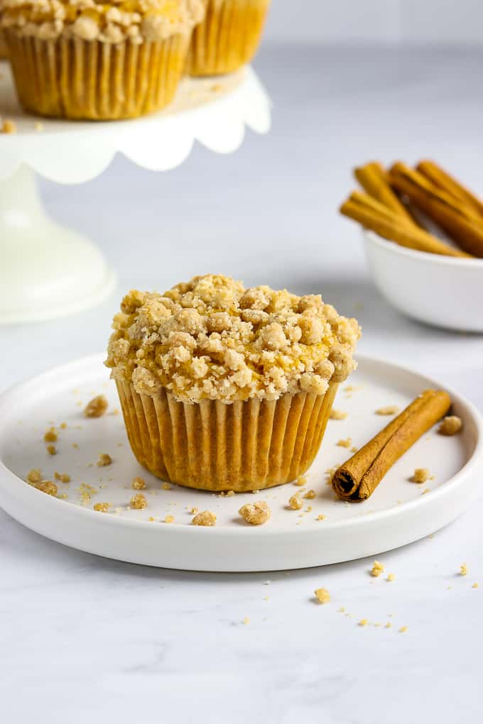 Fully baked muffin on a white plate with crumbs and a cinnamon stick on the side.