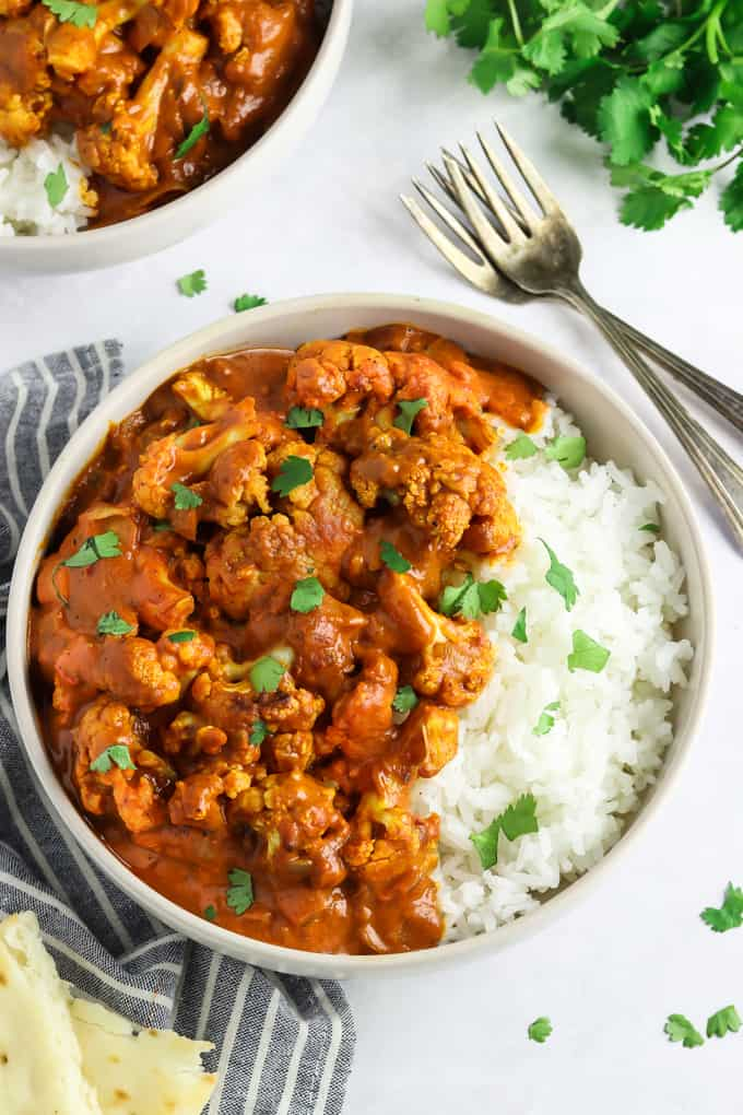 overhead view of two bowls of cauliflower tikka masala over rice. Topped with cilantro.