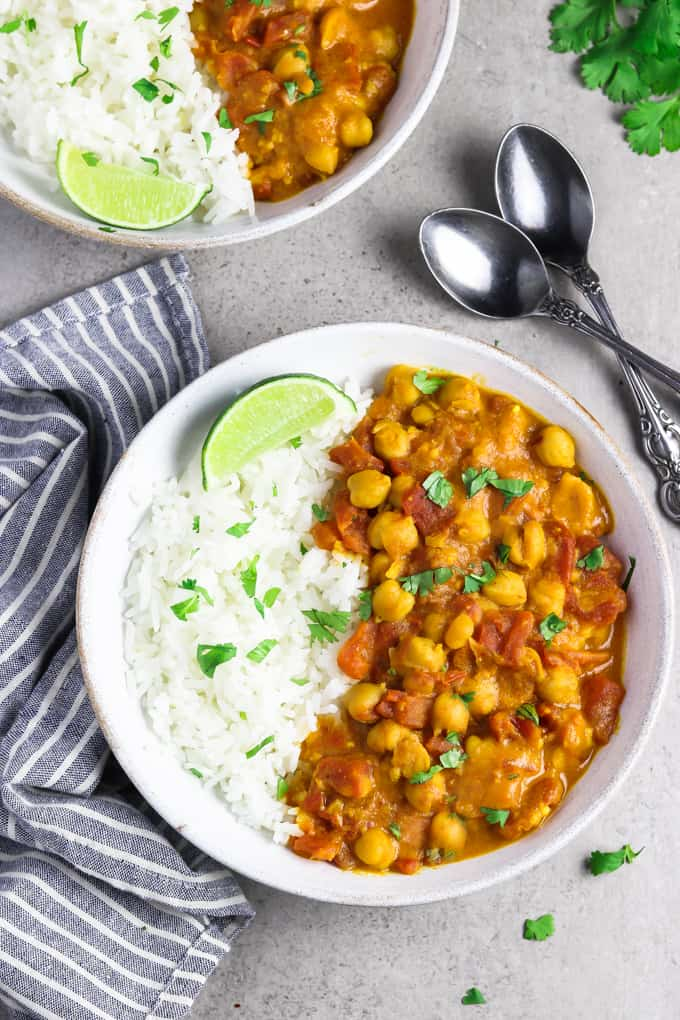 Two white bowls of vegan chickpea curry, topped with cilantro and lime wedges.