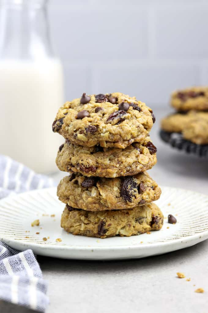 Stack of Oatmeal Raisin Chocolate Chip Cookies on a white plate. Bottle of milk in the background.