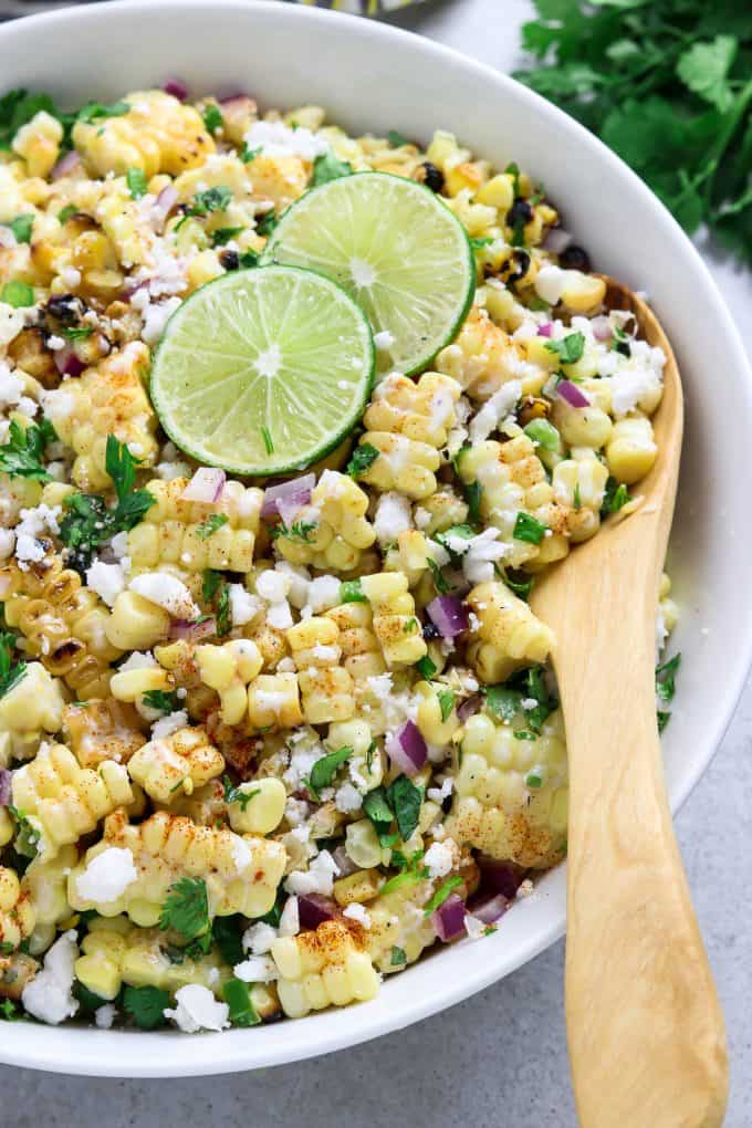 Close up view of Mexican corn salad in a white serving bowl with wooden spoon inside.
